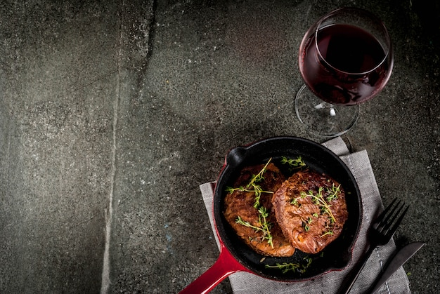 Domowe steki z grilla z tymiankiem na porcji patelni, z widelcem, nożem i lampką wina na czarnym kamiennym stole