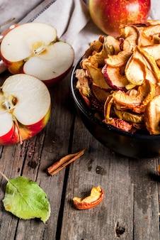 Domowe suszone na słońcu organiczne jabłka pokrajają chrupiące chipsy jabłkowe na starym rustykalnym drewnianym stole ze świeżym jabłkiem i cynamonem