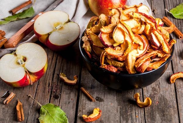 Domowe suszone organiczne plasterki jabłka, chrupiące chipsy jabłkowe na starym rustykalnym drewnianym stole ze świeżym jabłkiem i cynamonem. copyspace