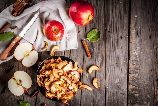 Domowe suszone organiczne plasterki jabłka, chrupiące chipsy jabłkowe na starym rustykalnym drewnianym stole ze świeżym jabłkiem i cynamonem. widok z góry lato