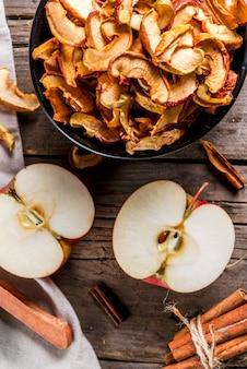 Domowe suszone organiczne plasterki jabłka, chrupiące chipsy jabłkowe na starym rustykalnym drewnianym stole ze świeżym jabłkiem i cynamonem. widok z góry
