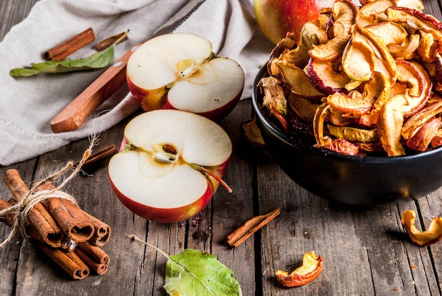 Domowe suszone organiczne plasterki jabłka, chrupiące chipsy jabłkowe na starym rustykalnym drewnianym stole ze świeżym jabłkiem i cynamonem.