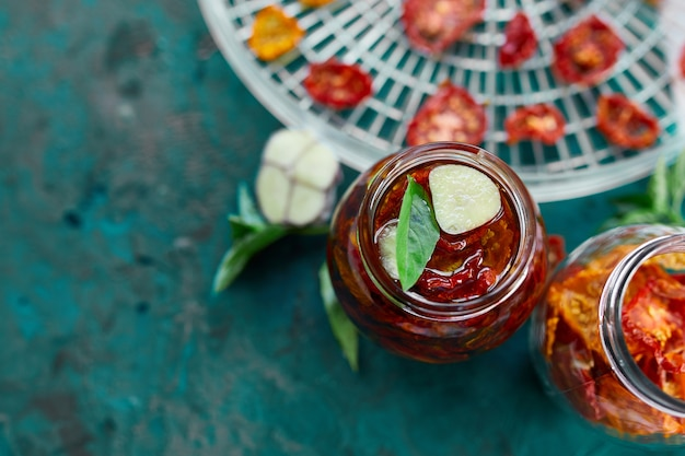 Domowe suszone pomidory z ziołami, czosnek w oliwie z oliwek w szklanym słoiku na ciemnozielonym tle. widok z góry. druk do kuchni