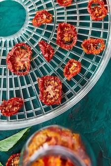 Domowe suszone pomidory z ziołami, na sicie z suszarki na zielonym tle. widok z góry, miejsce na kopię, płaski układ