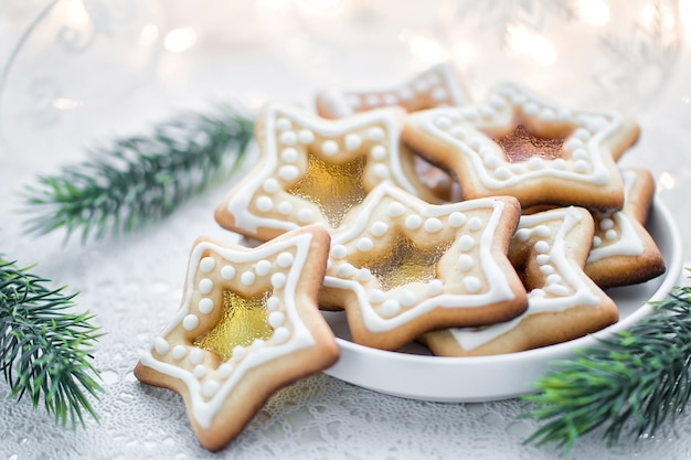 Domowe świąteczne ciasteczka karmelowe w kształcie gwiazdy na białym tle z gałązkami jodły
