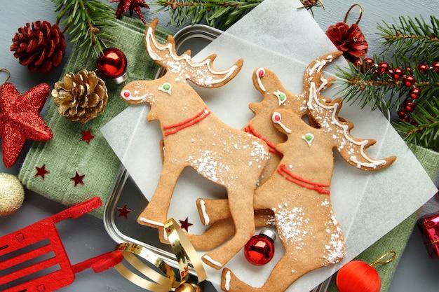 Domowe świąteczne ciasteczka w kształcie łosia z świąteczną dekoracją.