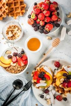 Domowe świeże belgijskie miękkie wafle z miodem, świeżymi owocami, orzechami i jagodami
