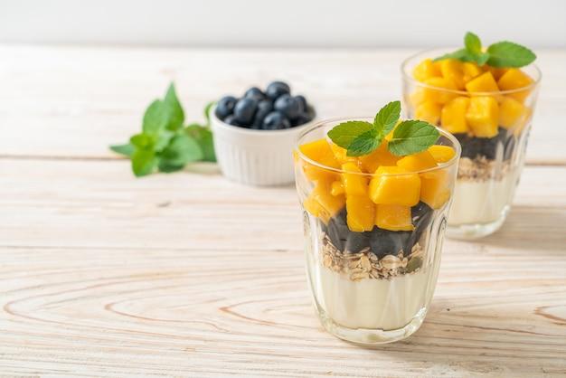 Domowe świeże mango i świeża jagoda z jogurtem i muesli - styl zdrowej żywności