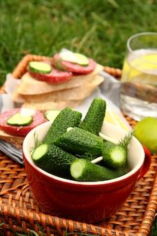 Domowe świeże solone ogórki w misce i kanapki z wędzoną kiełbasą