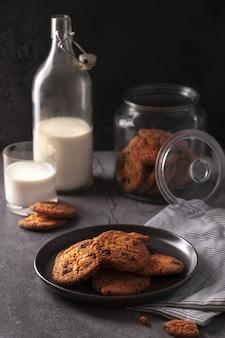 Domowe świeżo upieczone ciasteczka z kawałkami czekolady z butelką mleka