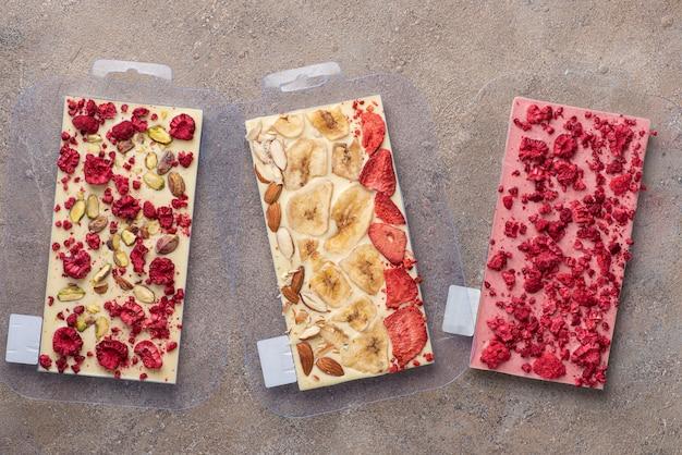 Domowe tabliczki czekolady z liofilizowanymi jagodami i orzechami w foremkach
