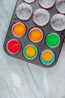 Domowe tęczowe babeczki na dwóch blachach piekarnika. widok z góry.
