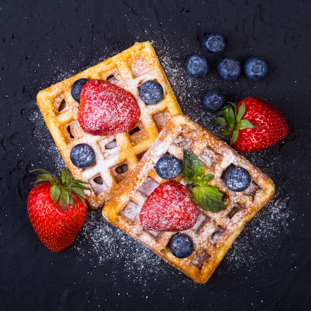 Domowe tradycyjne belgijskie gofry ze świeżymi owocami, jagodami i cukrem w proszku na czarnej płycie.