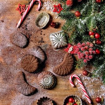 Domowe tradycyjne bożonarodzeniowe kruche ciasteczka czekoladowe półksiężyce z kakaowym cukrem pudrem z foremkami do ciastek, jodła, ozdoby czerwonych gwiazdek świątecznych. drewniane tło. płaski, kwadratowy