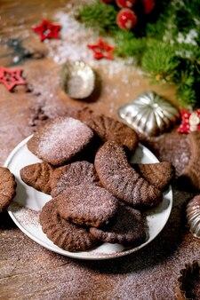 Domowe tradycyjne świąteczne ciasteczka kruche czekoladowe półksiężyce z kakaowym cukrem pudrem na talerzu ceramicznym z foremkami do ciastek, jodła, ozdoby z czerwonych gwiazd bożonarodzeniowych na drewnianym tle