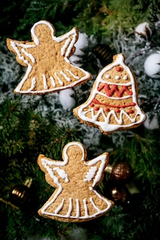 Domowe tradycyjne świąteczne pierniki z ozdobnym lukrem. aniołki z piernika i dzwonek z dekoracjami świątecznymi i jodłą