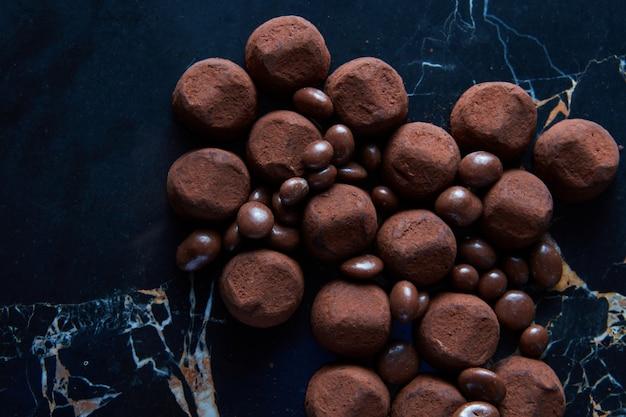 Domowe trufle czekoladowe na czarnym marmurowym tle.