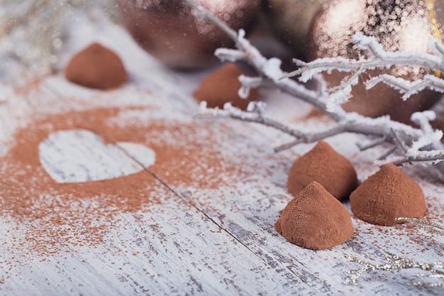 Domowe trufle z ciemnej czekolady z proszkiem kakaowym w kształcie serca i zimową dekoracją na białym rustykalnym drewnianym stole. zimowe wakacje tło.