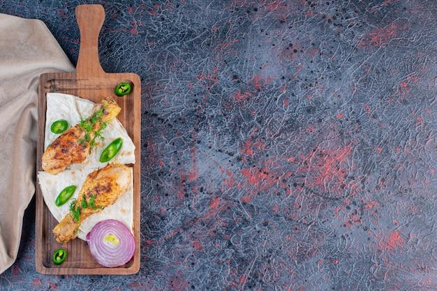 Domowe udka z kurczaka z grilla na drewnianej desce do krojenia