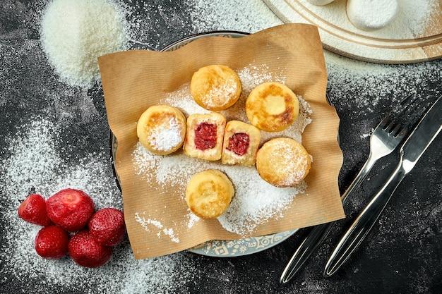 Domowe ukraińskie serniki z nadzieniem owocowym na papierze rzemieślniczym na ciemnym stole. zamknij widok na syrniki, selektywna ostrość