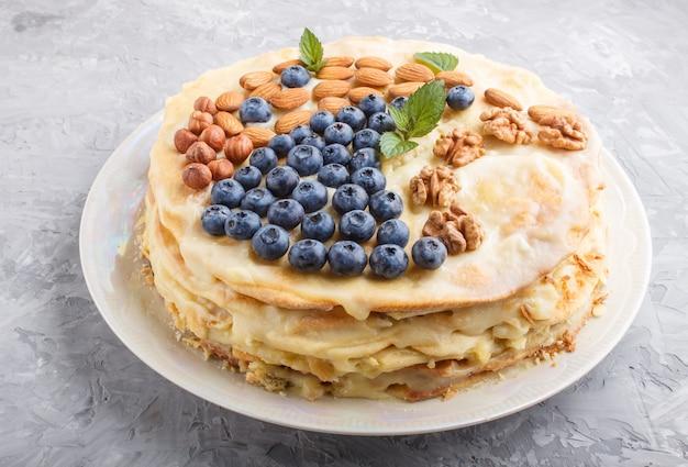 Domowe warstwowe ciasto napoleon ze śmietaną mleczną. ozdobiony jagodami, migdałami, orzechami włoskimi, orzechami laskowymi, miętą na widoku z boku szarej powierzchni betonu.