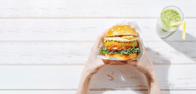 Domowe wegańskie burgery z bezglutenową bułką i kotletem na bazie warzyw oraz zielonym smoothie