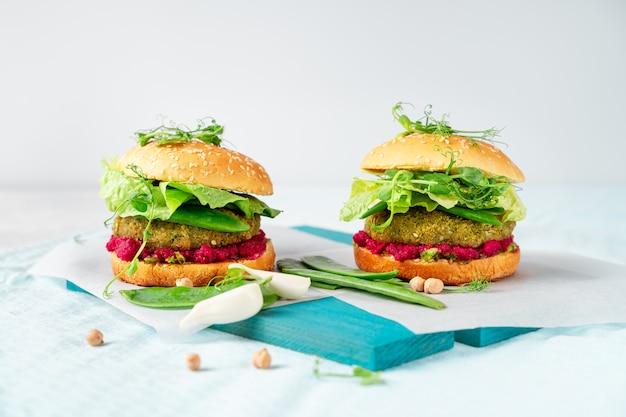 Domowe wegańskie burgery z pasztetem z ciecierzycy, groszkiem i hummusem z buraków
