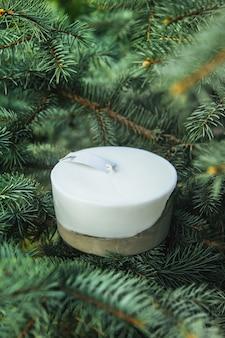 Domowe wielokolorowe świece z betonem na powierzchni zielonych igieł