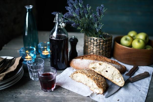 Domowe wino w butelce i kieliszku, świeży chleb i noże na serwetce, miska z jabłkami, stos talerzy i koszyczek z bukietem niebieskich polnych kwiatów