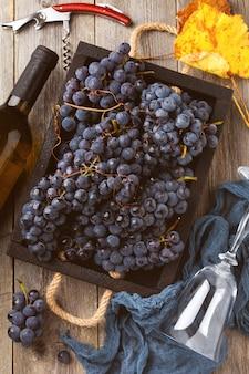 Domowe winogrona w czarnym pudełku, butelka wina i korkociąg na starym drewnianym tle. zabytkowy styl. stonowany obraz.widok z góry
