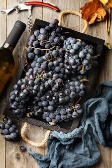 Domowe winogrona w czarnym pudełku, butelka wina i korkociąg na starym drewnianym