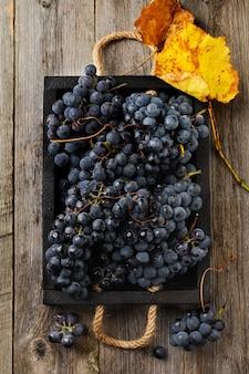 Domowe winogrona w czarnym pudełku na starym drewnianym