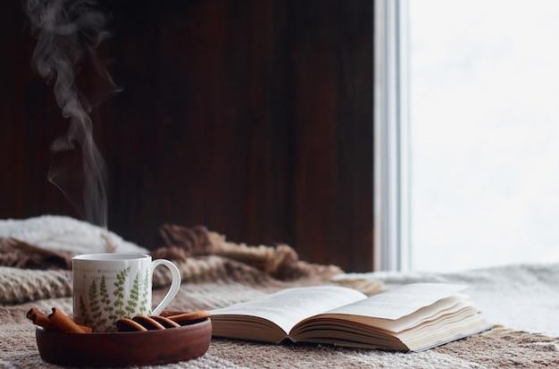 Domowe wnętrze salonu. wełniany koc i filiżanka herbaty z parą. śniadanie na kanapie w porannym słońcu. przytulna koncepcja jesień lub zima. komfort hyugge
