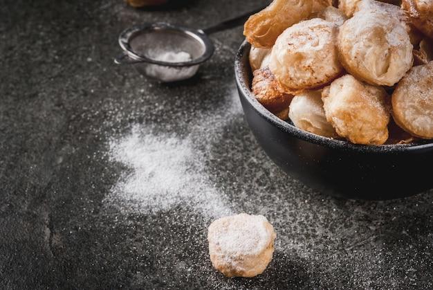 Domowe wypieki, ciasta francuskie. modne jedzenie. popcorn z cronutów, dziury z francuskiego pączka w czarnej misce i papierowej torbie