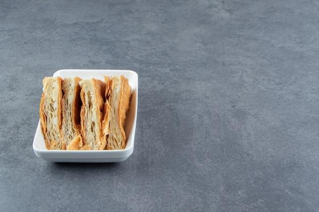Domowe wypieki z serem na białym talerzu.
