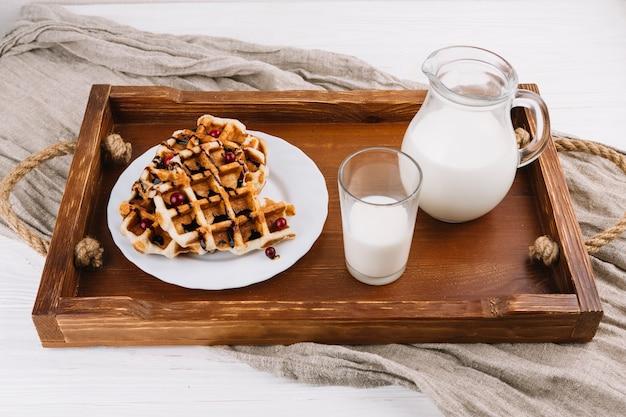 Domowej roboty belgijscy gofry z świeżym mlekiem na drewnianej tacy