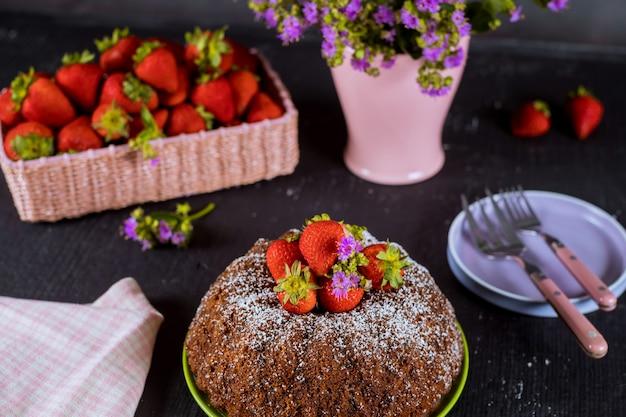 Domowej roboty bundt tort z świeżymi truskawkami, talerzem, wazą z kwiatami.