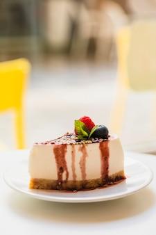 Domowej roboty cheesecake z świeżymi jagodami i mennicą dla deseru na talerzu