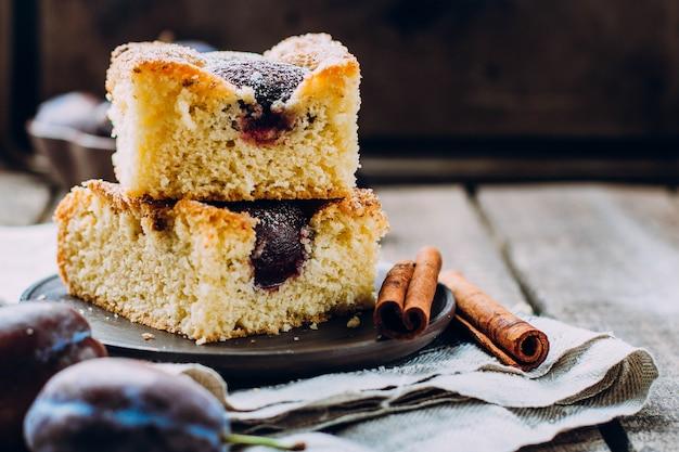 Domowej roboty ciasto ze śliwkami na tle drewniany stół. owocowy jesień tort z cynamonem.