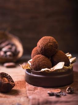 Domowej roboty czekoladowe trufle na drewnianym stołowym zbliżenie widoku. smaczne wegetariańskie cukierki lub kulki z surowym kakao w proszku