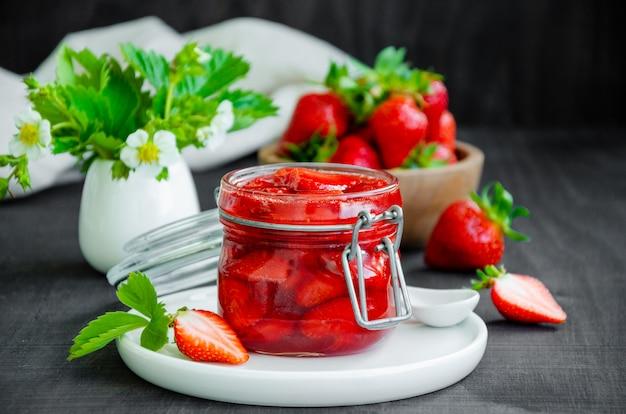 Domowej roboty dżem truskawkowy w szklanym słoju ze świeżymi truskawkami