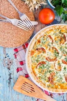 Domowej roboty francuski quiche kulebiak z pomidorem, serem i ziele na talerzu na drewnianym stole. widok z góry