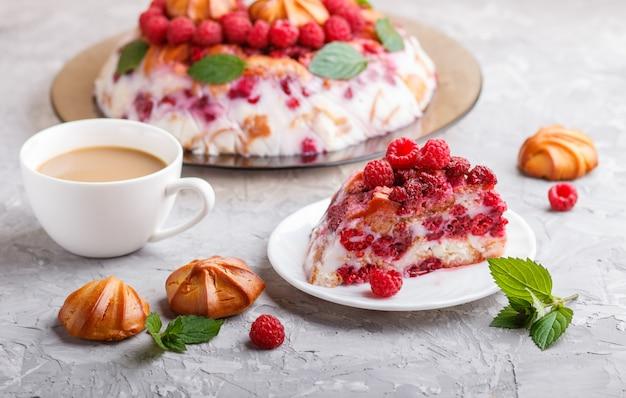 Domowej roboty galaretowy tort z mlecznymi ciastkami i malinką na szarym betonowym tle z filiżanką kawy