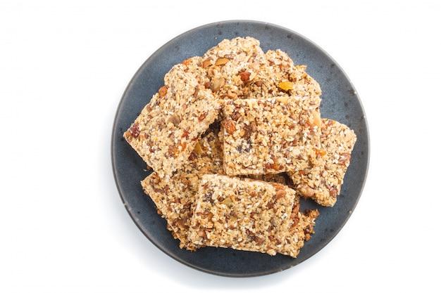 Domowej roboty granola od płatków owsianych dat wysuszone morelowe rodzynki dokrętki w błękitnym ceramicznym talerzu odizolowywającym na białym tle
