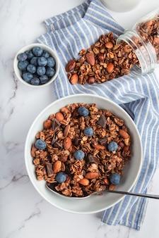 Domowej roboty granola z orzechami ciemnej czekolady i jagodami w misce na białym marmurowym tle