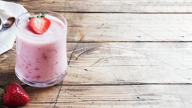 Domowej roboty jogurt z świeżymi truskawkami w szkłach na drewnianym tle. selektywne ustawianie ostrości. skopiuj miejsce