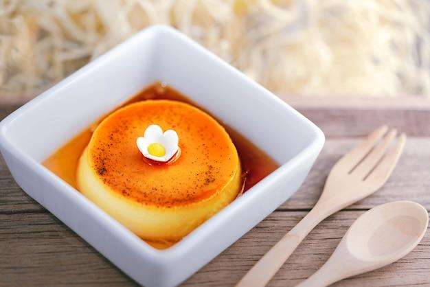 Domowej roboty karmelu kremu pudding na bielu talerzu z drewnianym tłem