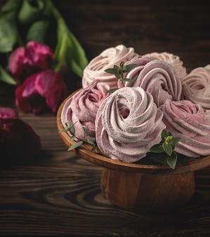 Domowej roboty marshmallows na stojaku i kwiatów tulipanach na drewnianym stole