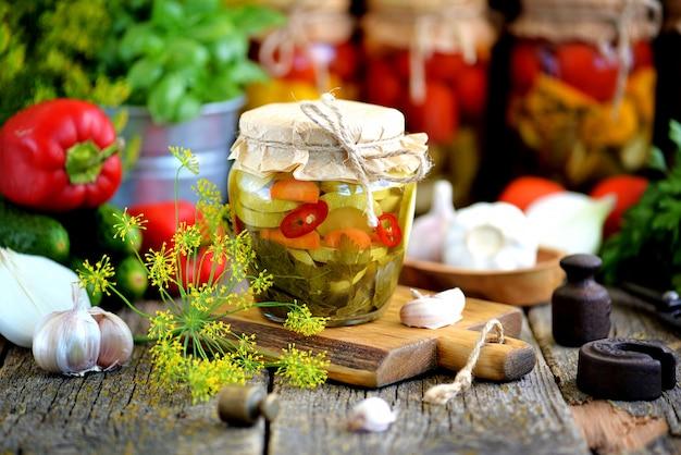 Domowej roboty marynowana cukinia z chili, koperkiem, marchewką, czosnkiem i cebulą w słoiku na starym drewnianym tle. styl rustykalny.