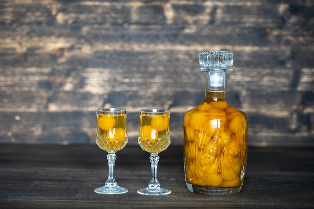 Domowej roboty nalewka z żółtej wiśni śliwki w kryształowej butelce i dwa kieliszki do wina na drewnianym stole, ukraina, z bliska. koncepcja napojów alkoholowych jagód